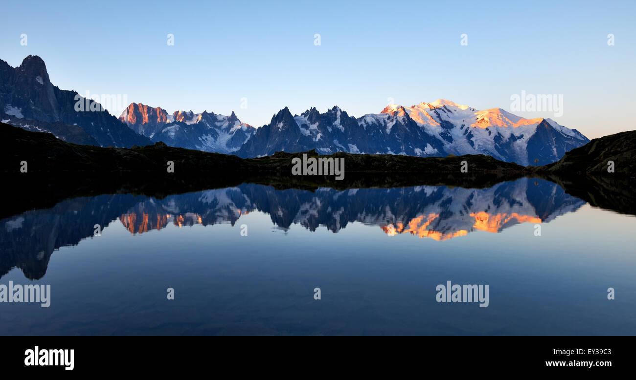 Mont Blanc massif at sunrise reflected in Lac de Chésserys, Aiguilles de Chamonix on the left, Montblanc on - Stock Image