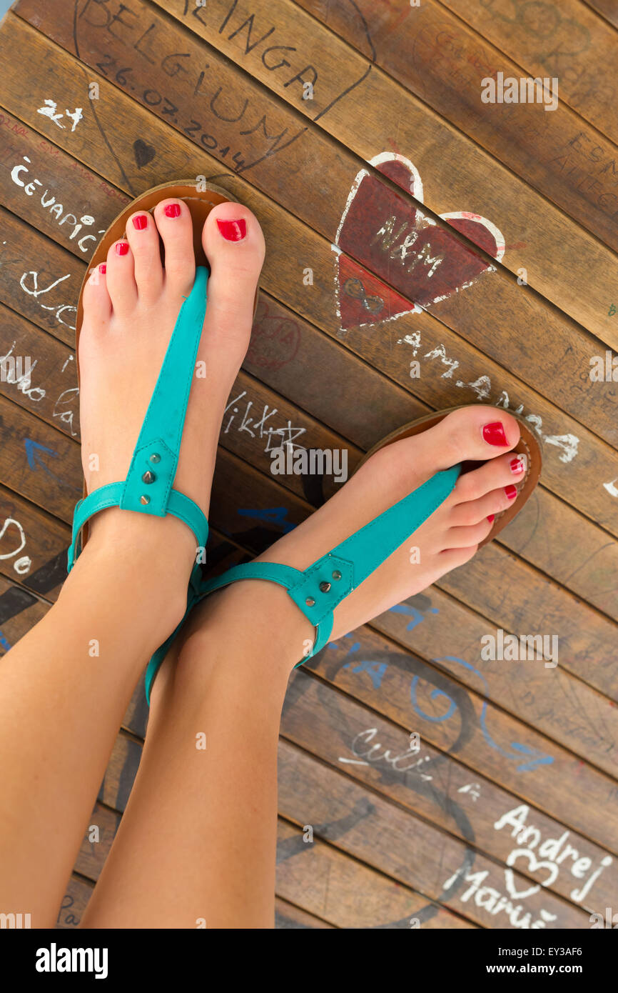 Female feet wearing turquoise sandals. - Stock Image