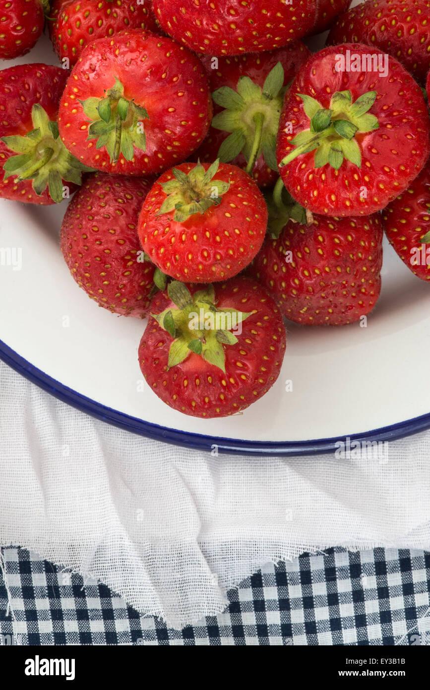 Fresh juicy strawberries on vintage enamelware on rustic background - Stock Image