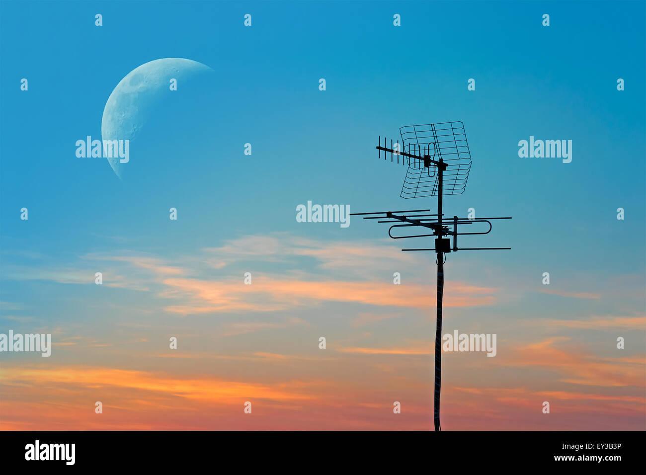 tv antenna under a huge moon at dusk - Stock Image