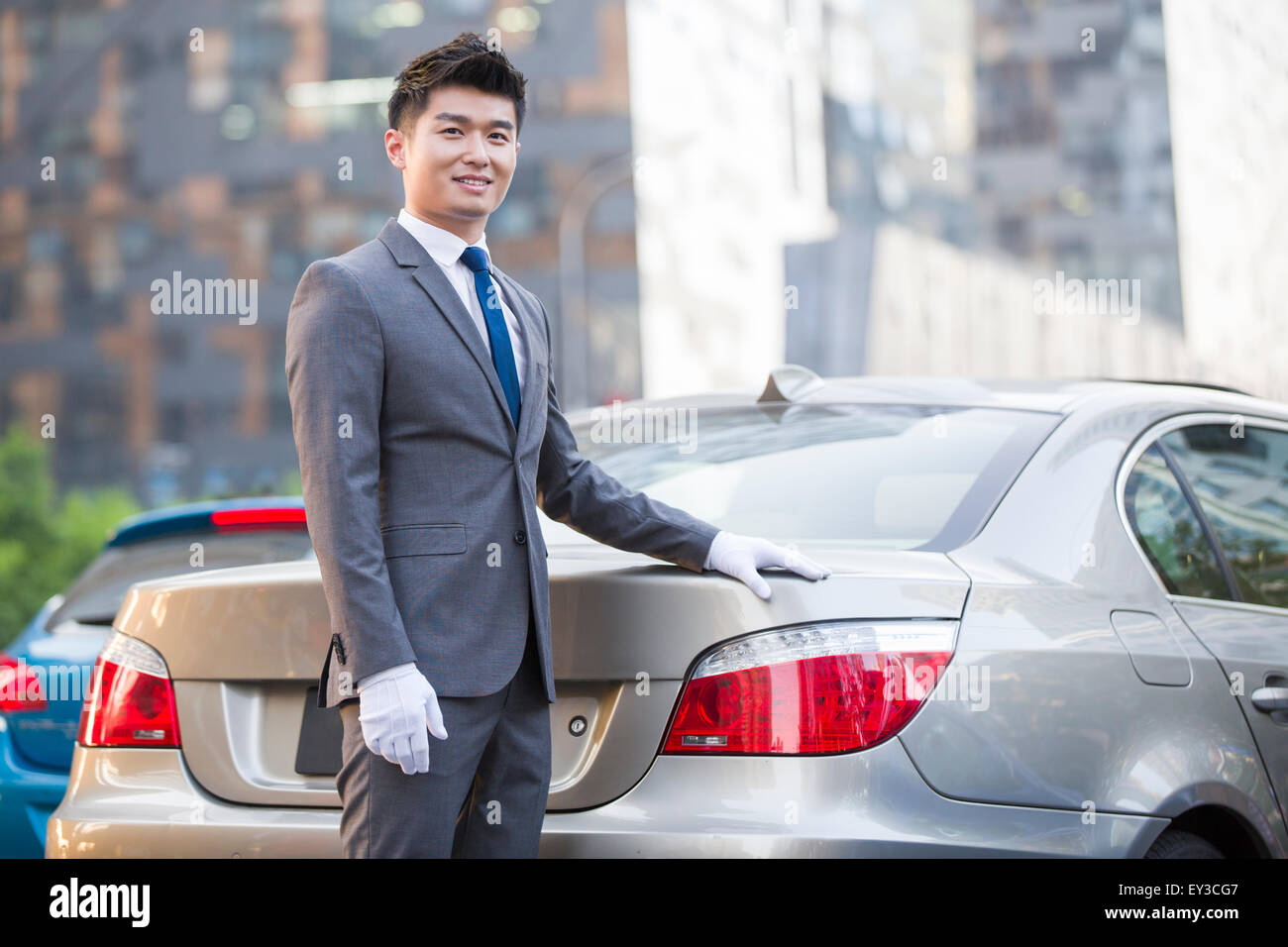 Chauffeur standing next to the car - Stock Image