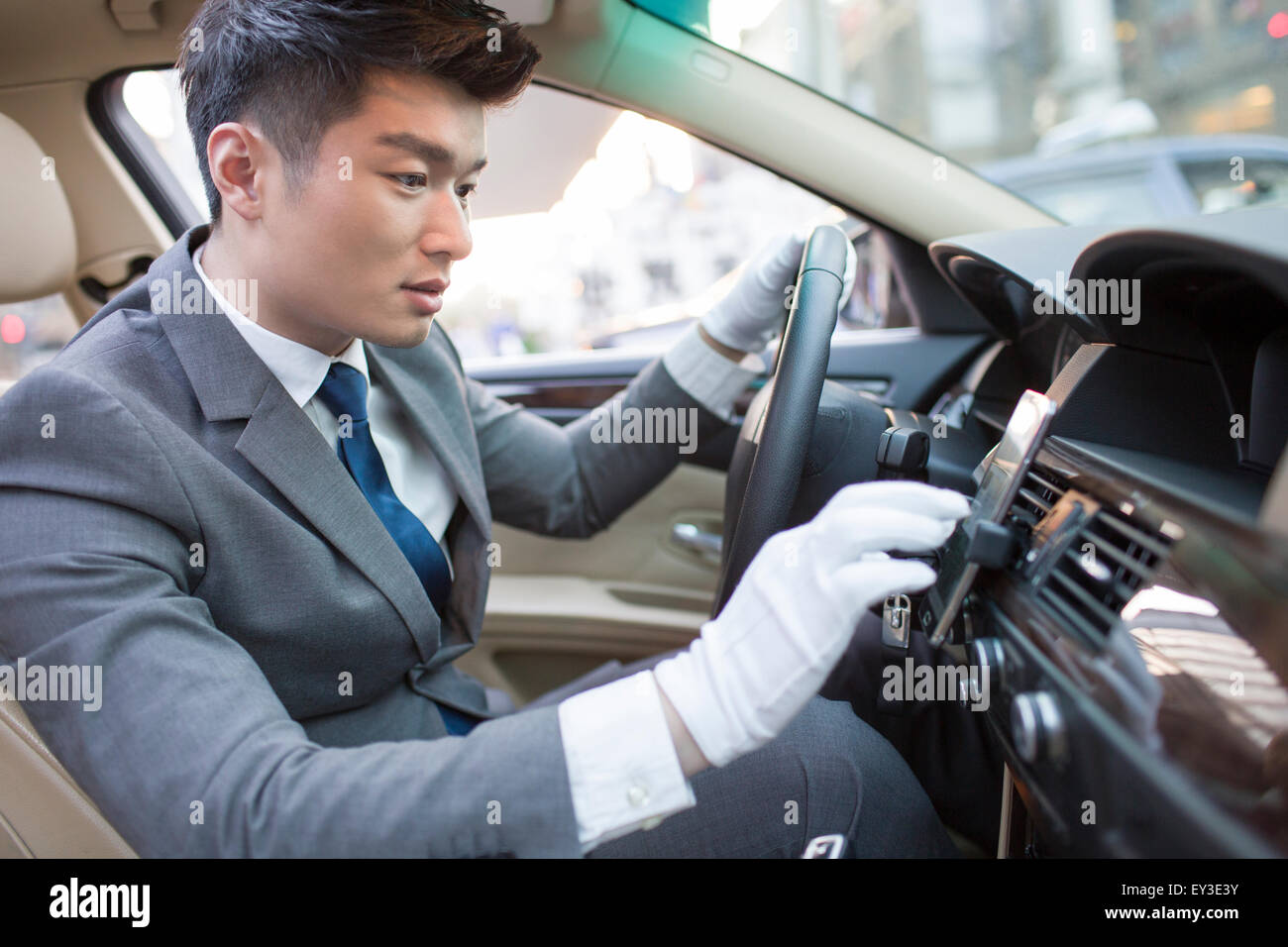 Chauffeur using smart phone as gps navigation for car - Stock Image
