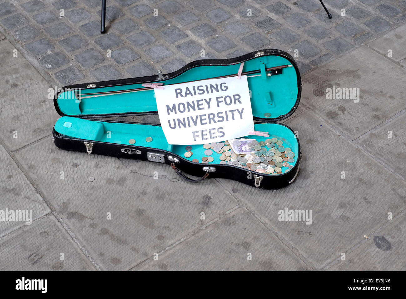 "A guitar case put on a pavement by two busker with a sign reading "" raising money for university fees"" - Stock Image"