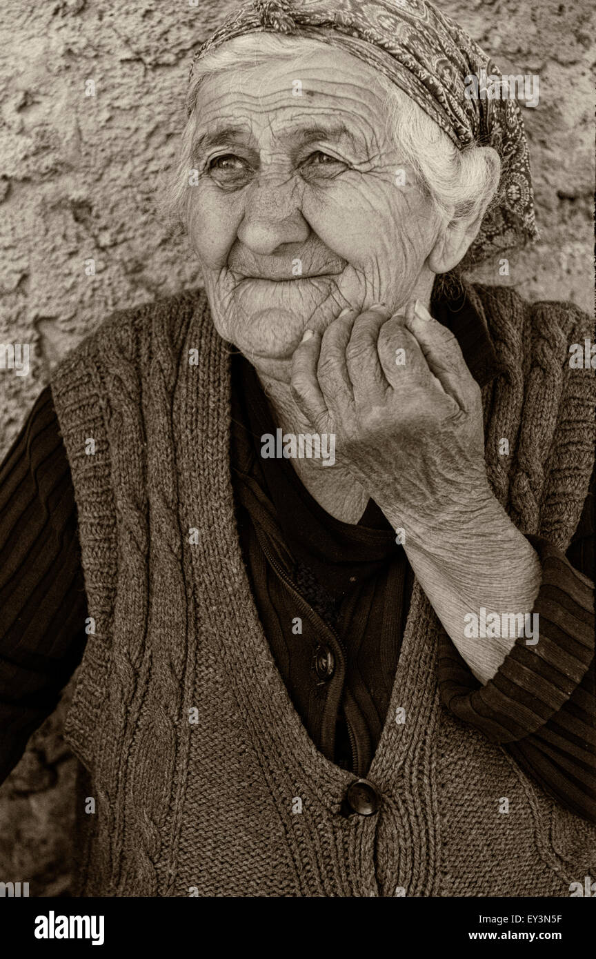 A documentary portrait of a senior citizen woman sat outside her house in rural Georgia, Eurasia. - Stock Image