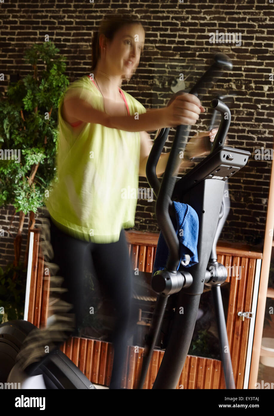 Young woman takes care of his health and she use elliptical trainer, intentional motion blur and narrow field of - Stock Image