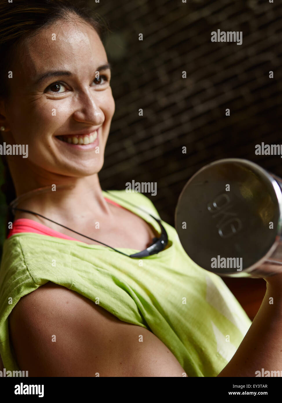 Young woman takes care of his health and she use dumbbell, intentional motion blur and narrow field of depth - Stock Image