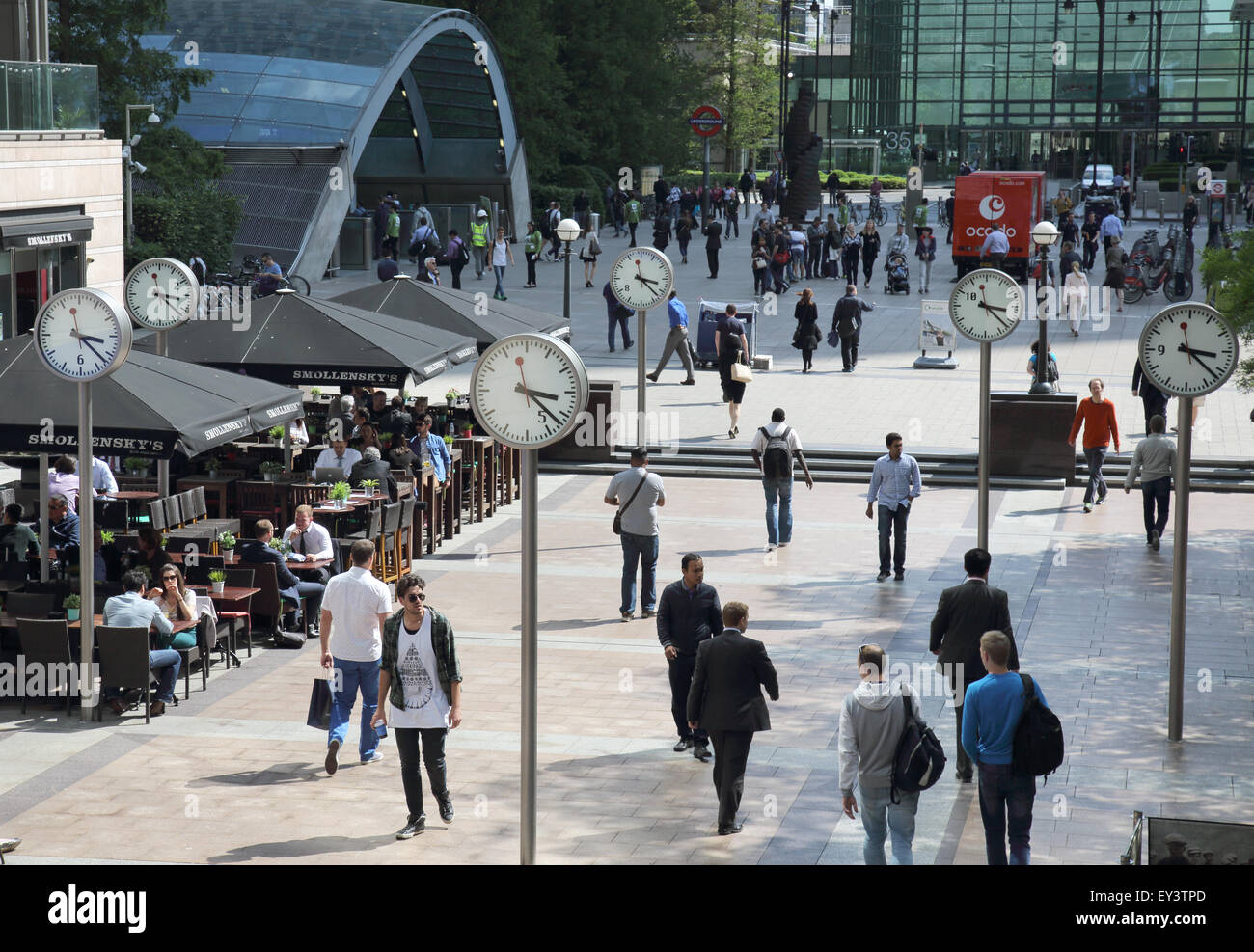 clocks outside canary wharf station in london docklands - Stock Image