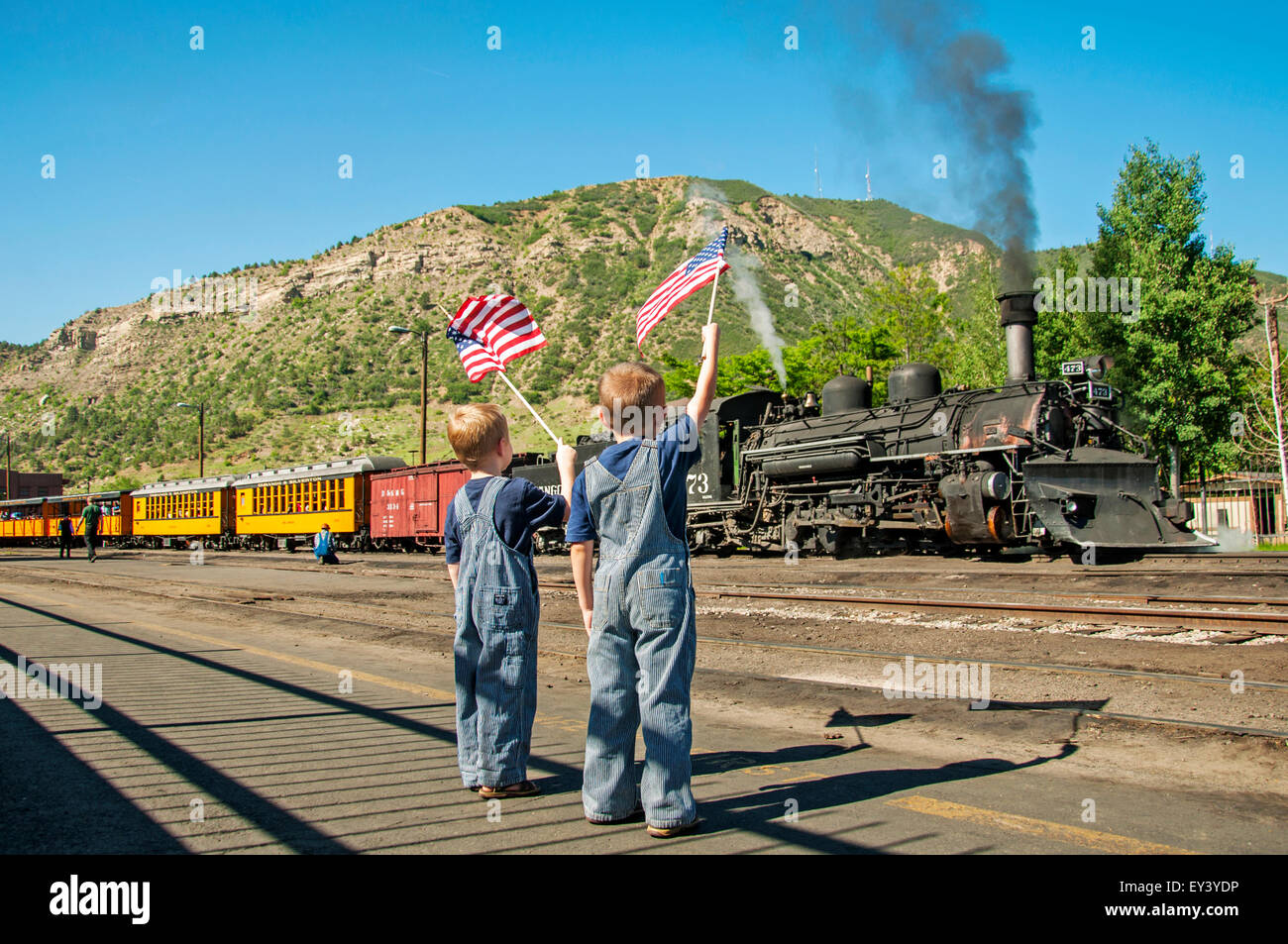 Boys wave American flags at departing train - Stock Image