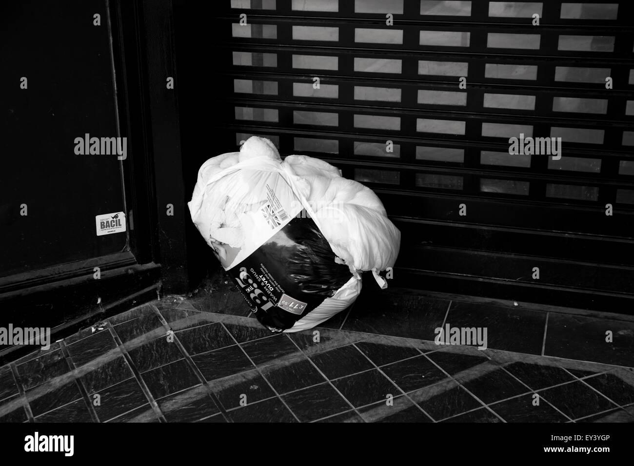 Homeless person's duvet left in a doorway - Stock Image