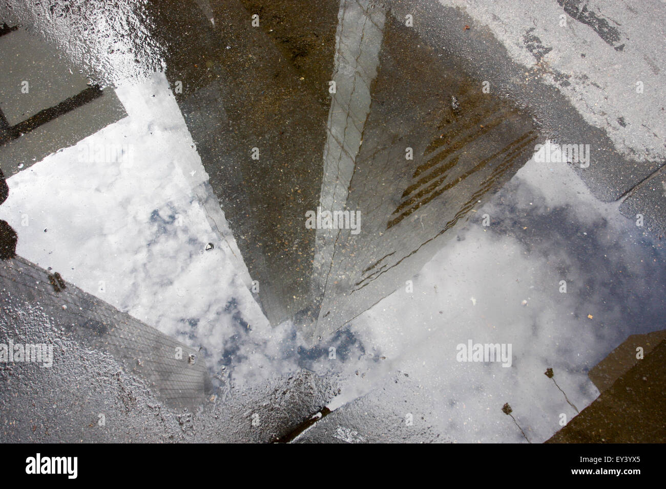 Manhattan skyscrapers reflecting in a rain puddle on the sidewalk. - Stock Image