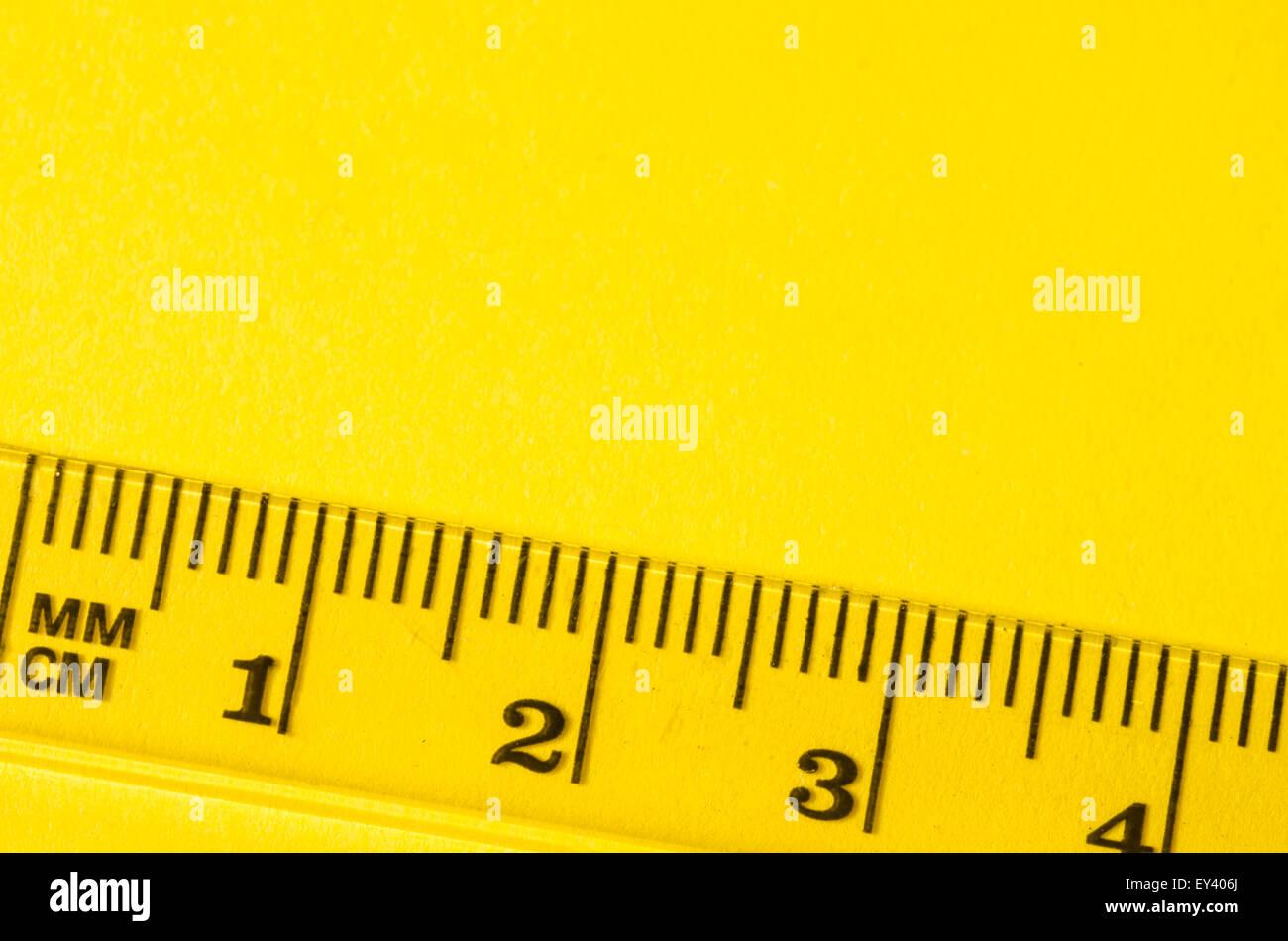 transparent ruler macro on paper background - Stock Image
