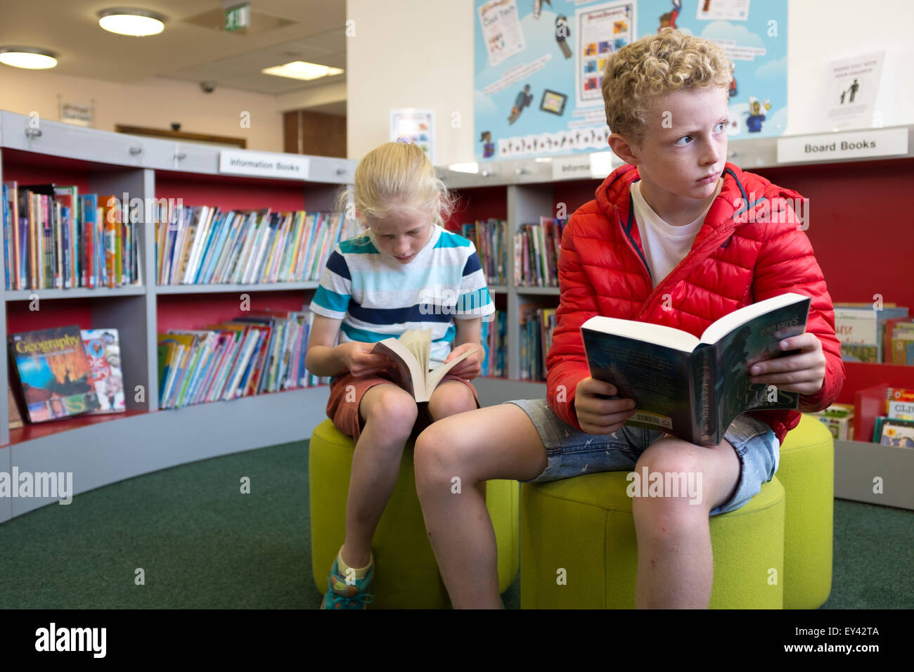 Yong boy and girl reading in the children's section of a public library - Stock Image