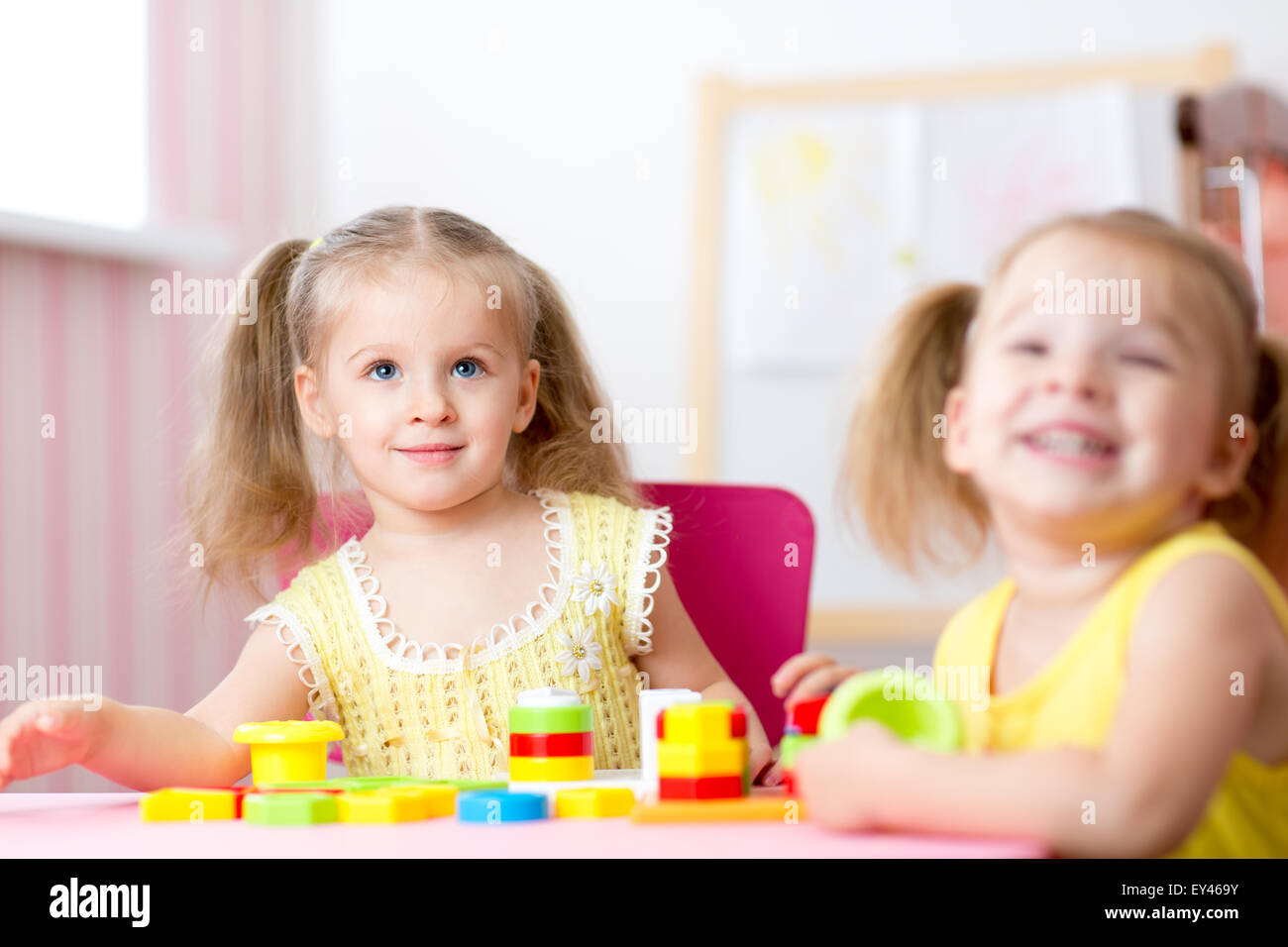 Kids playing with wooden blocks sitting at table in their room - Stock Image