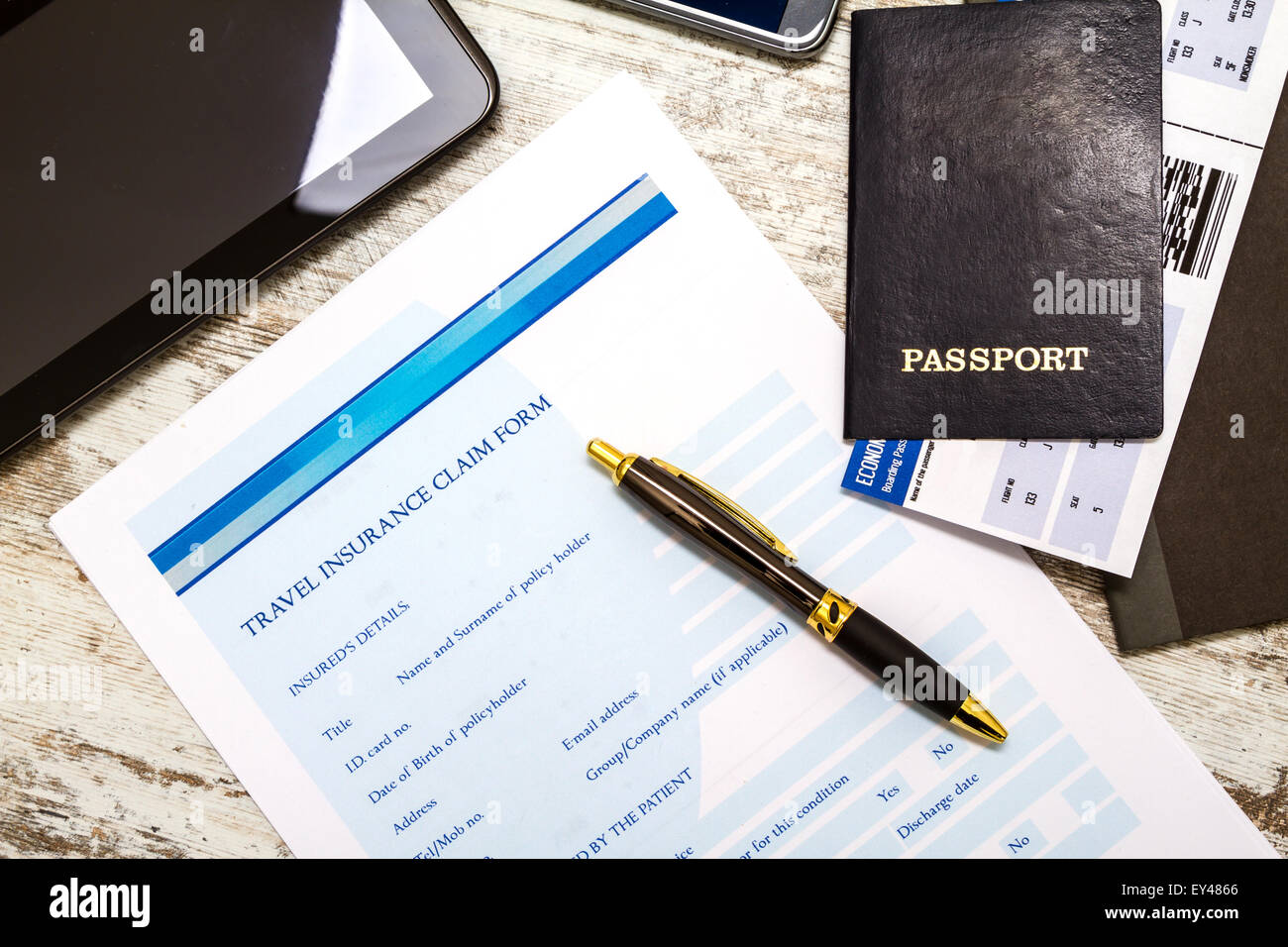 Travel insurance application form with a boarding pass and a passport - Stock Image