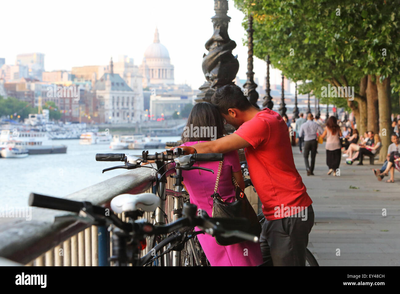 Romantic couple on the South Bank on a warm summer's evening, with St Paul's Cathedral behind, in London, - Stock Image