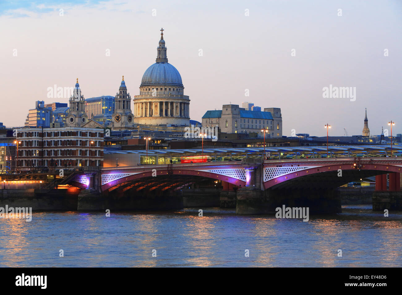 Blackfriars Railway Bridge, in front of St Paul's Cathedral, across the River Thames, at dusk, in London, UK - Stock Image