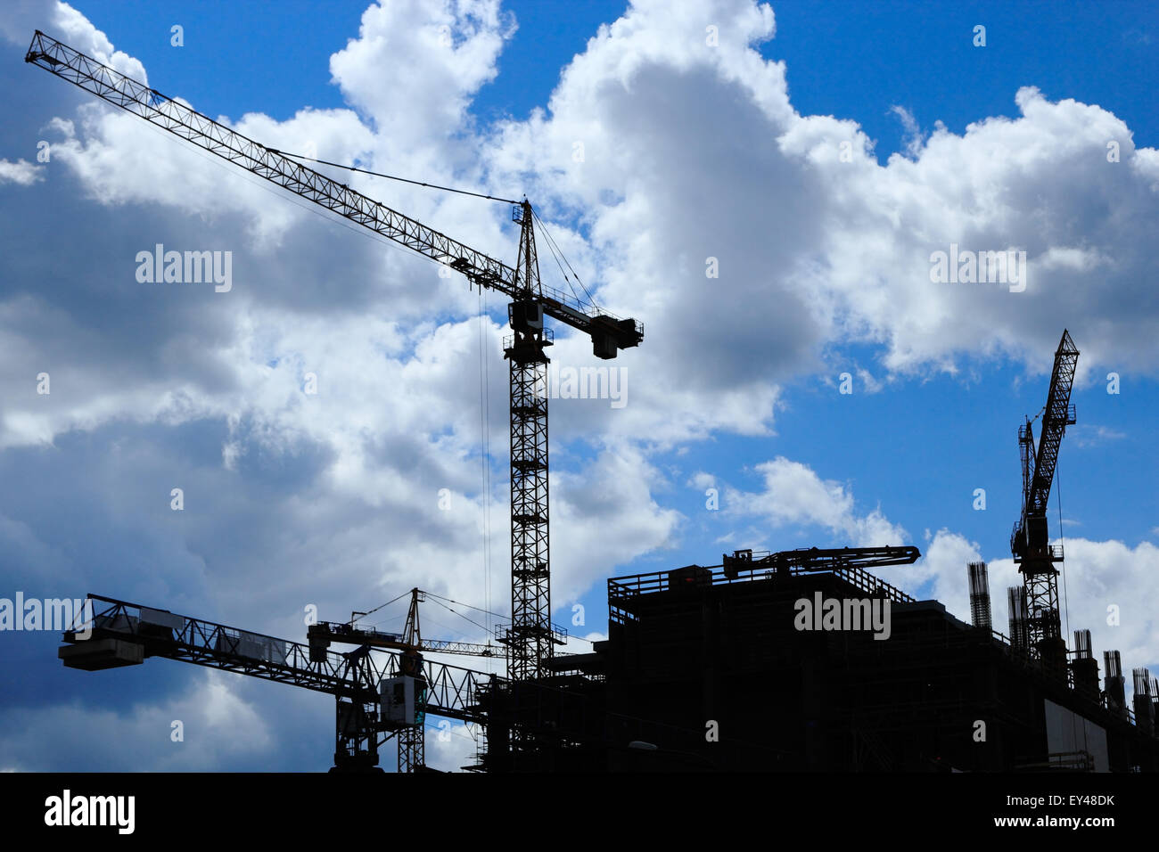 Construction site with a few cranes silhouetted against blue sky and clouds. - Stock Image