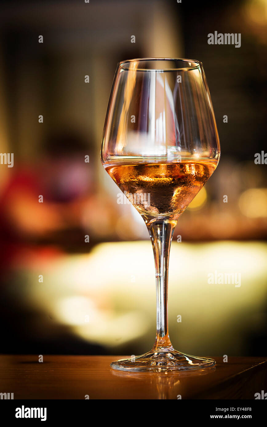 glass of rose wine on bar counter at night - Stock Image