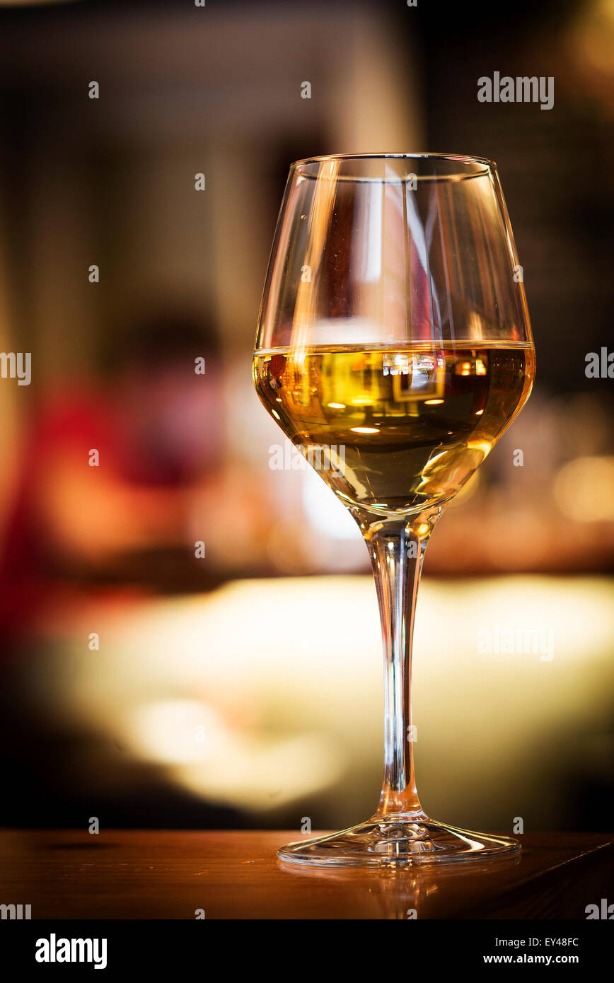 glass of white wine on bar counter at night - Stock Image