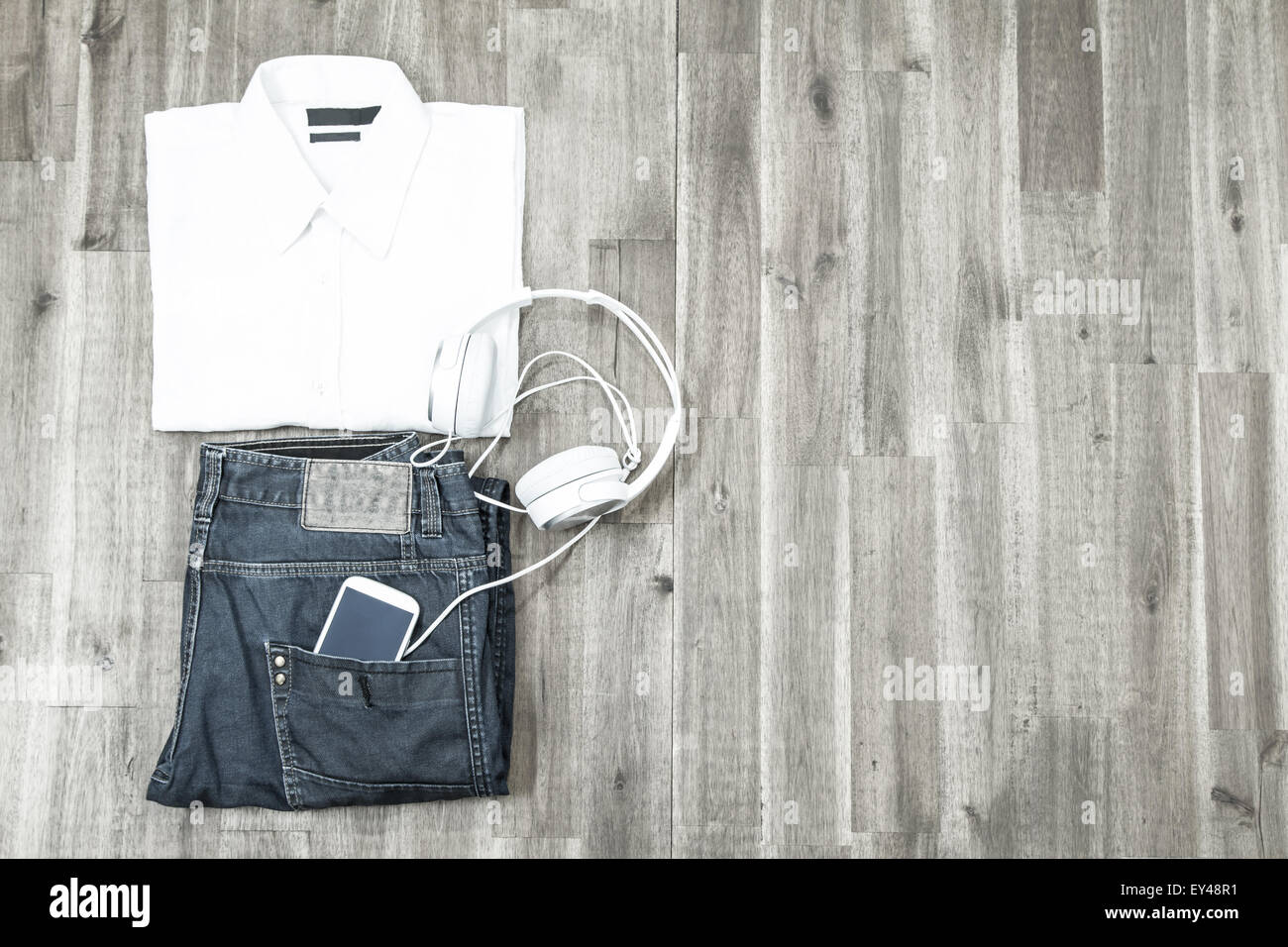 Informal male outfit with cellphone and headphone, background - Stock Image