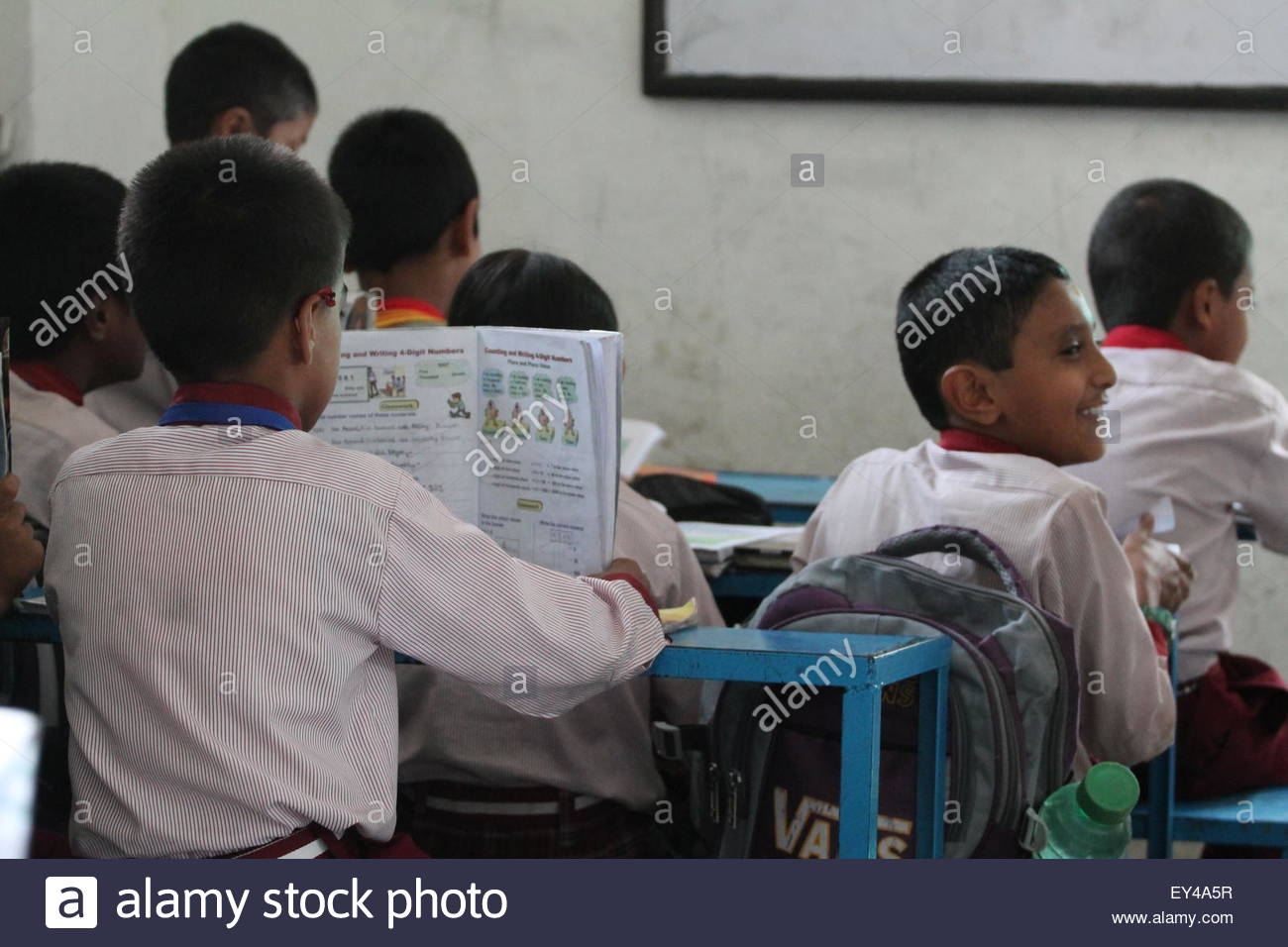 Bhaktapur, Nepal. July 20th, 2015. NEPAL, Bhaktapur:  A child reads a textbook in a classroom at Candid International - Stock Image