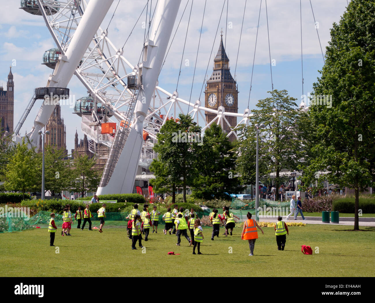 Children playing football outdoors in the Jubilee gardens, South bank, by the London Eye, Big Ben in the background, - Stock Image