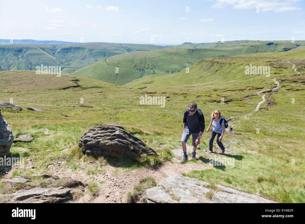 Walkers walking up Grindslow Knoll, on Kinder Scout, Derbyshire, Peak District, England, UK - Stock Image