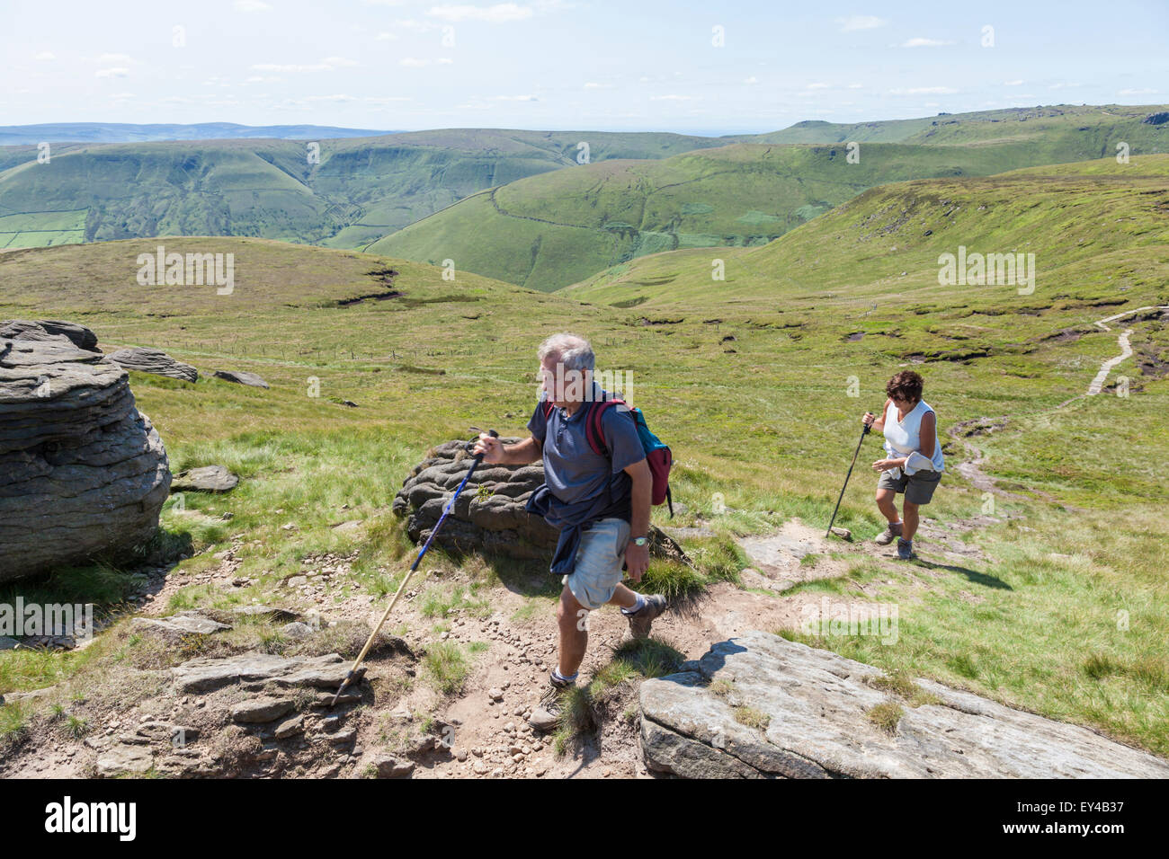 Hill walkers in the English countryside during Summer walking up Grindslow Knoll on Kinder Scout, Derbyshire, Peak - Stock Image