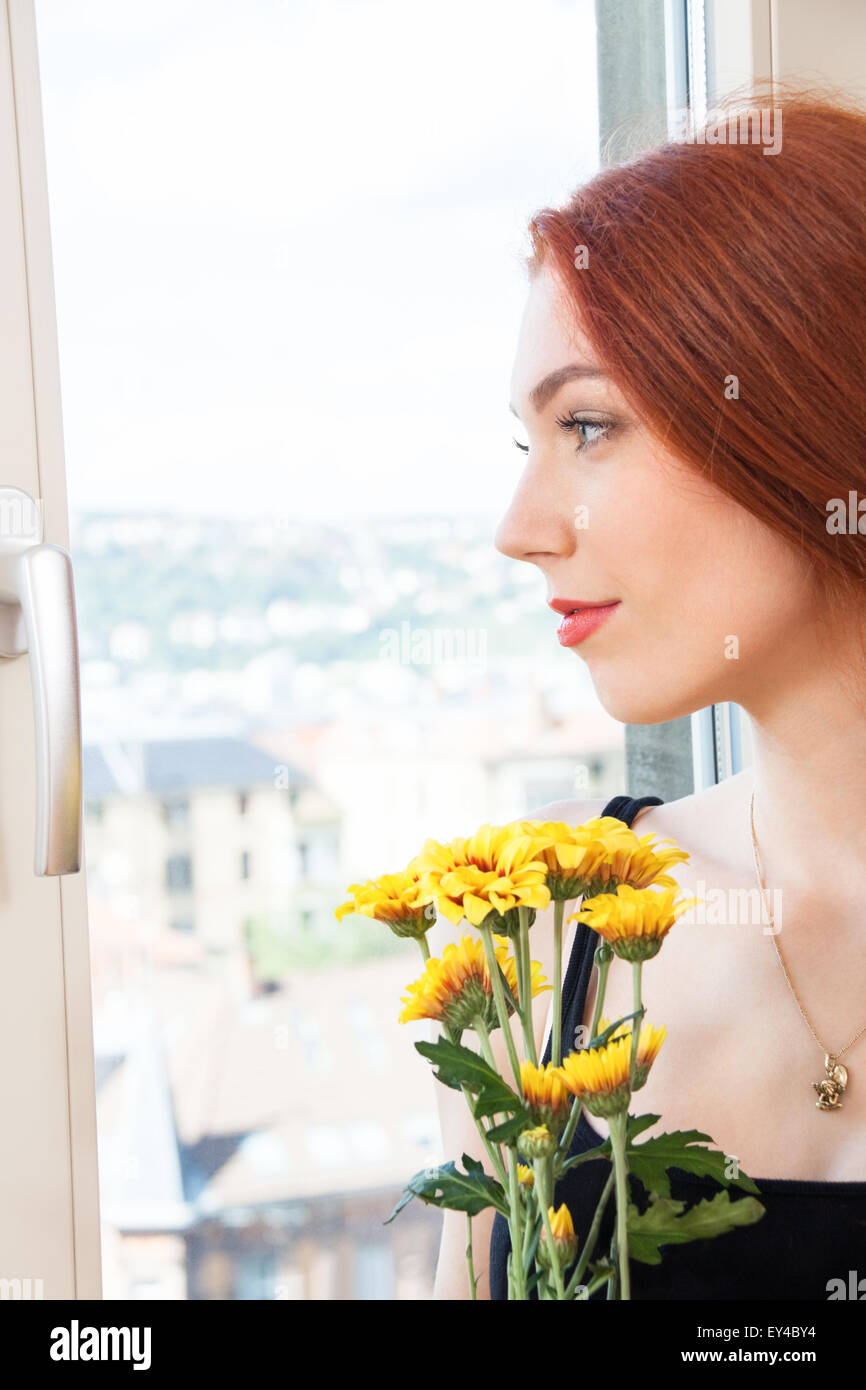 Close up Thoughtful Pretty Young Woman Holding Yellow Flowers, Looking Outside While Leaning on Glass Window. - Stock Image