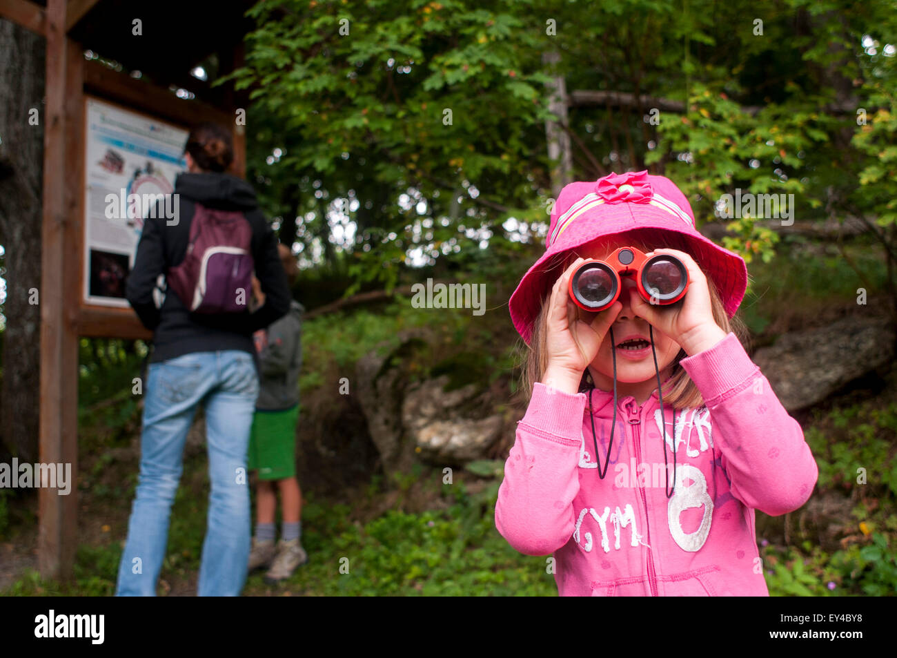 Young Girl Looking Through Binoculars While Woman and Young Boy Look at Hiking Map - Stock Image