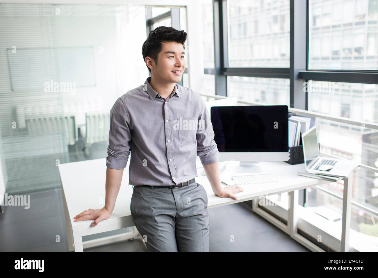 Young businessman looking through window in office - Stock Image