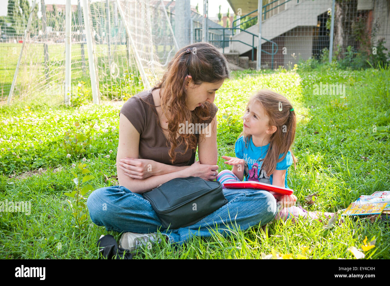 Woman and Child Playing While Sitting in Grass - Stock Image