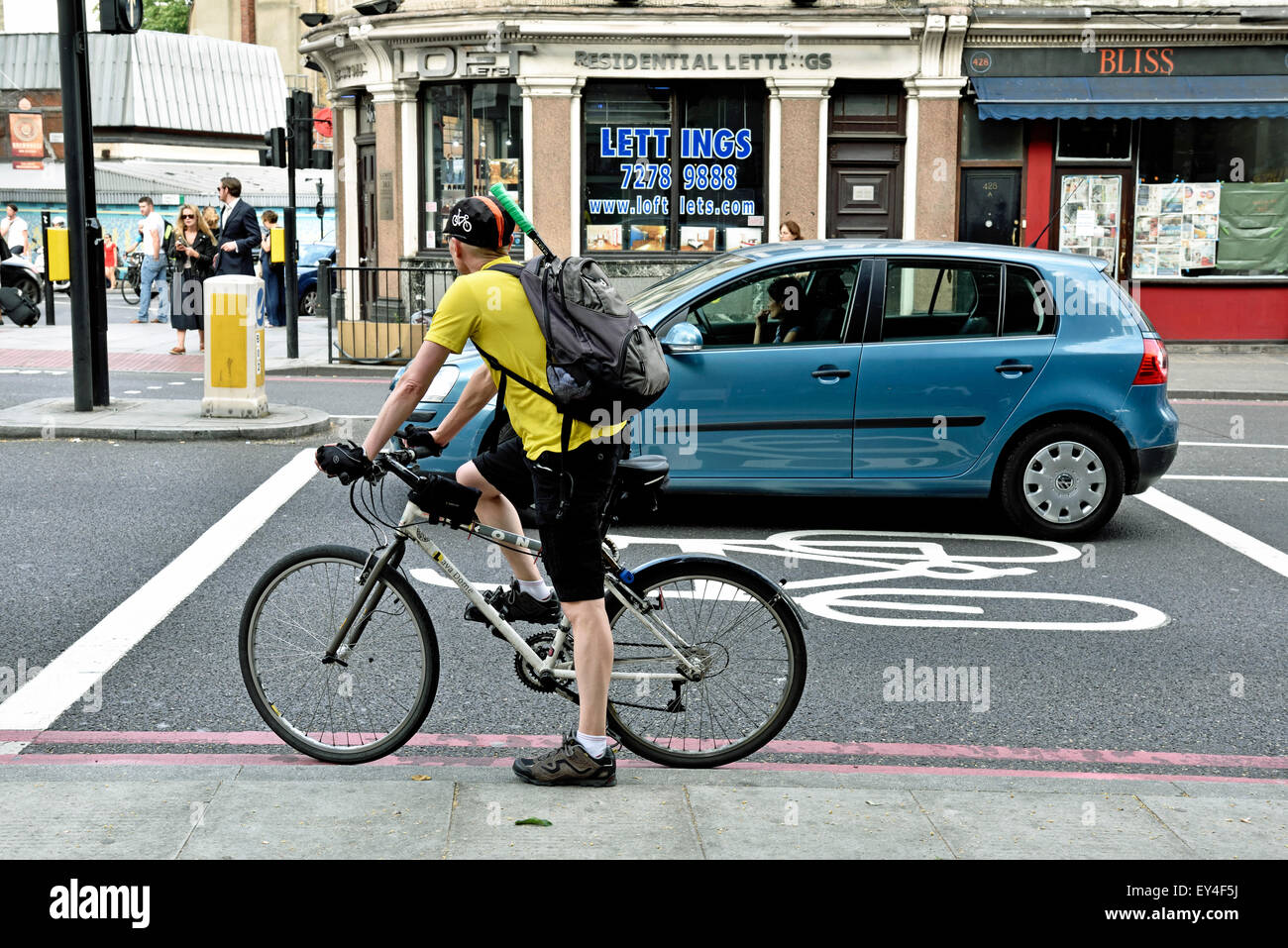 Commuter cyclist in advance stop lane alongside illegally positioned car, Angel, London Borough of Islington, England - Stock Image