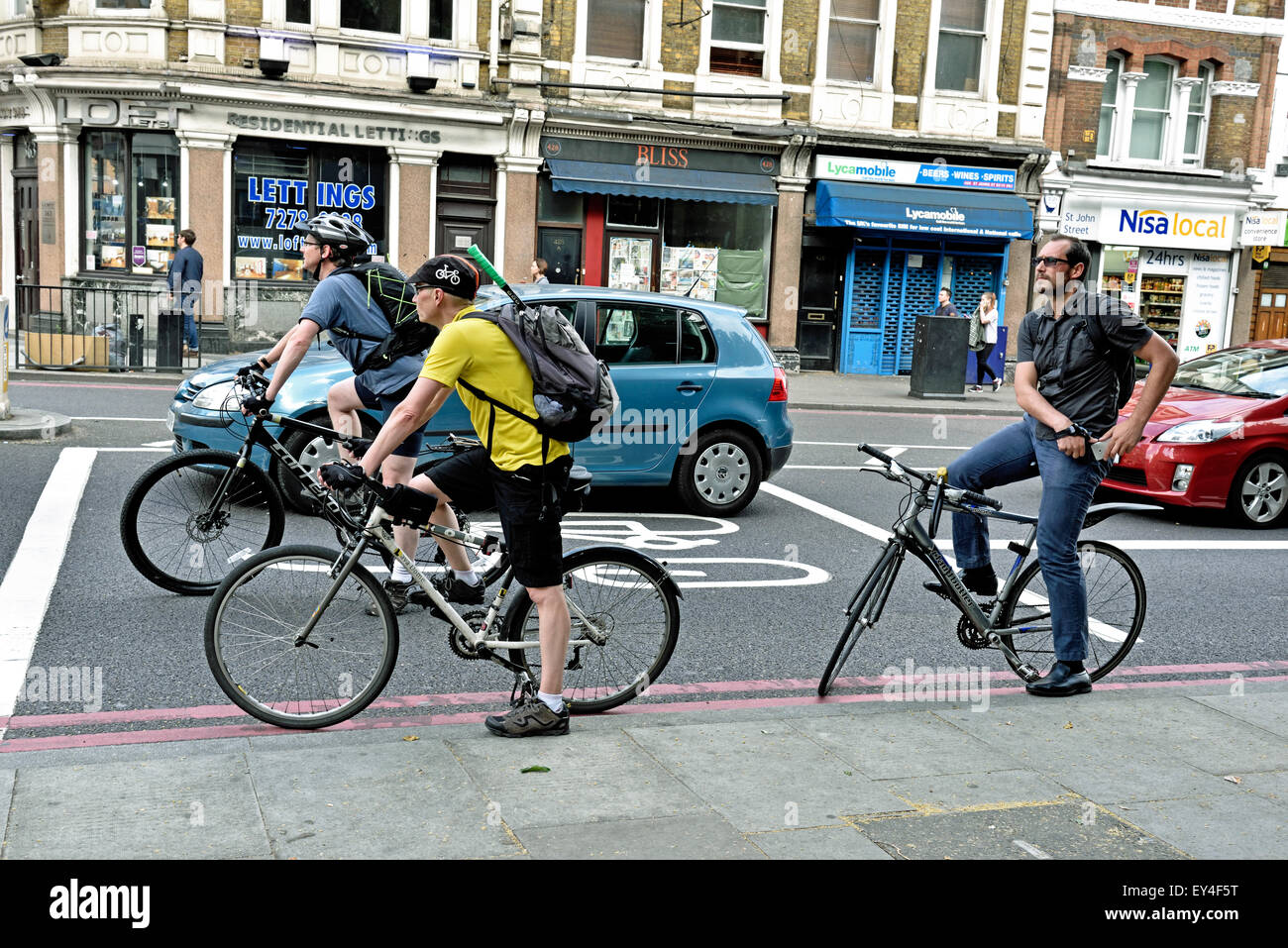 Commuter cyclists in advance stop lane alongside illegally positioned car, Angel, London Borough of Islington, England - Stock Image