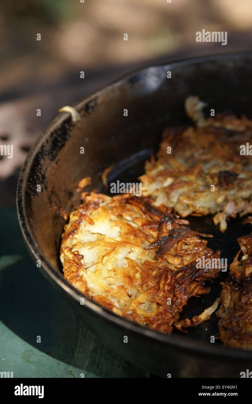 Hash brown potatoes cooking in an iron skillet outdoors. Vertical format with blurred background. - Stock Image
