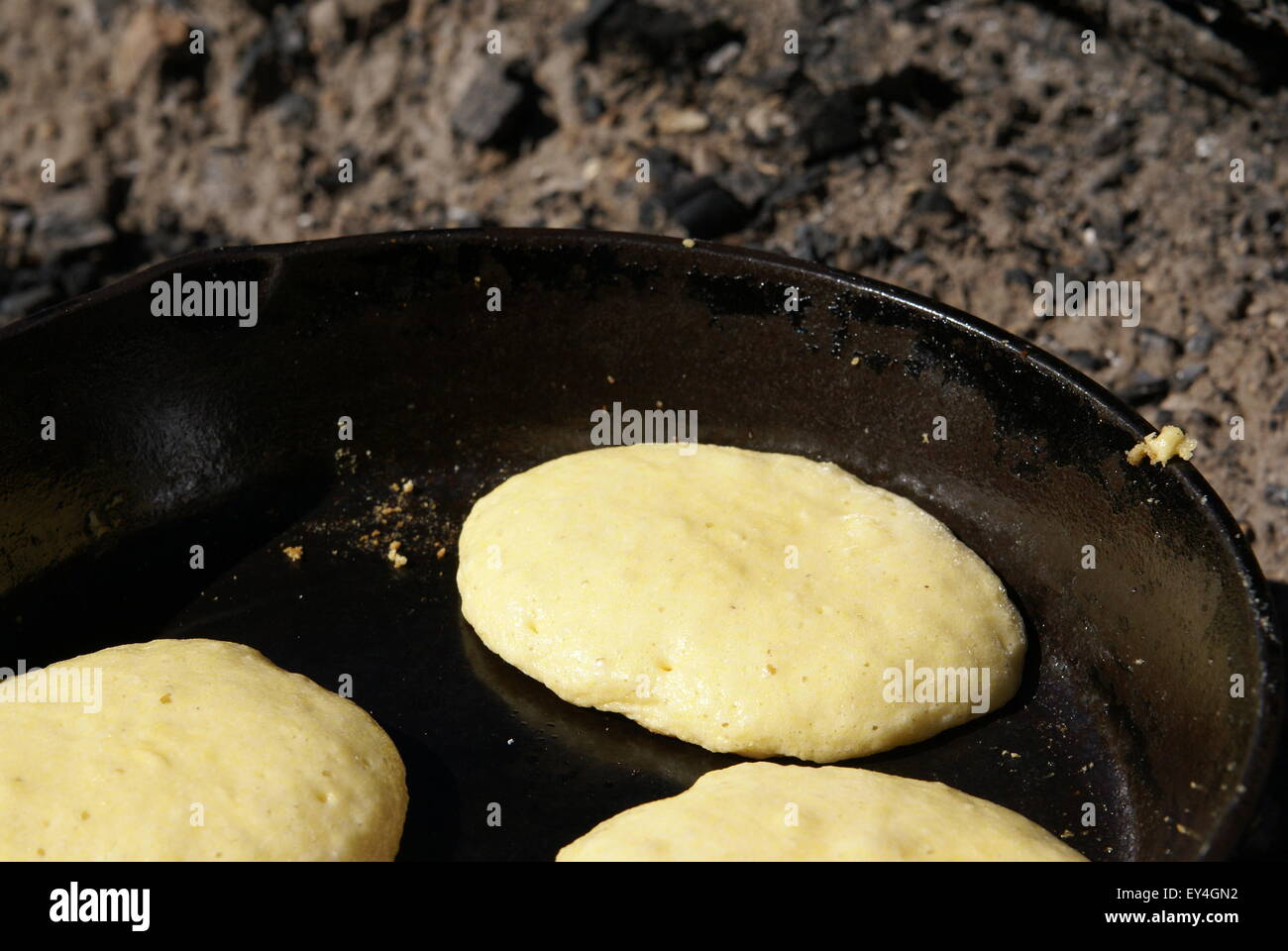 Cornmeal batter being cooked into pancakes in an iron skillet over an open fire - Stock Image