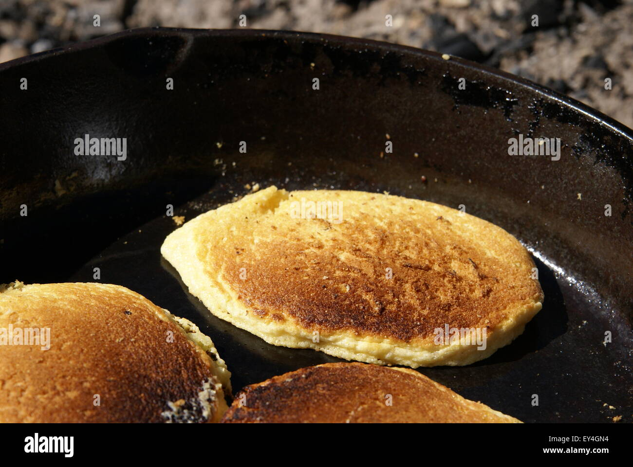 Cornmeal pancakes cooking in a cast iron skillet over an open fire outdoors. Close up view of cakes - Stock Image