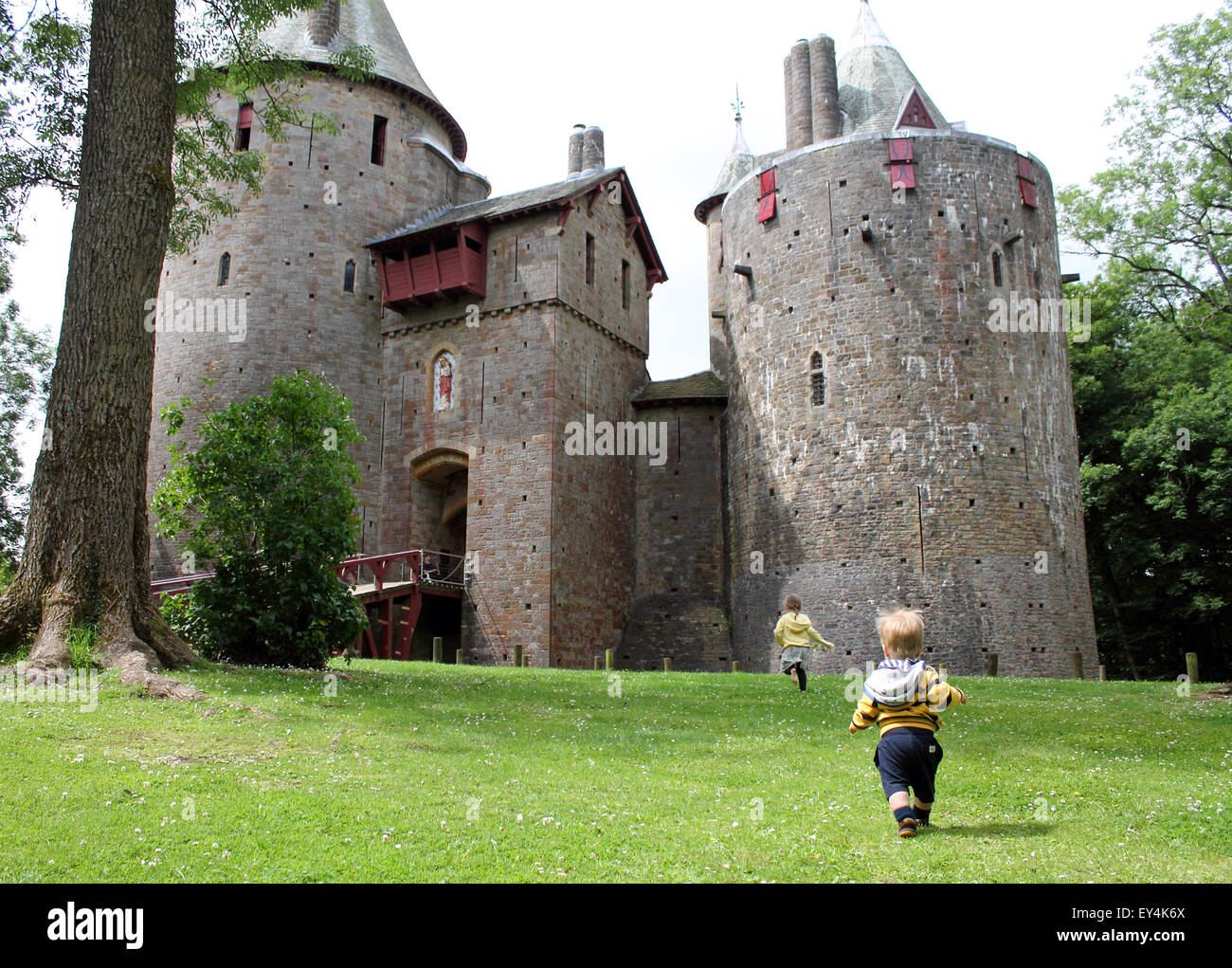 Young boy and girl running towards castle or Castell Coch, Cardiff, South Wales, UK - Stock Image