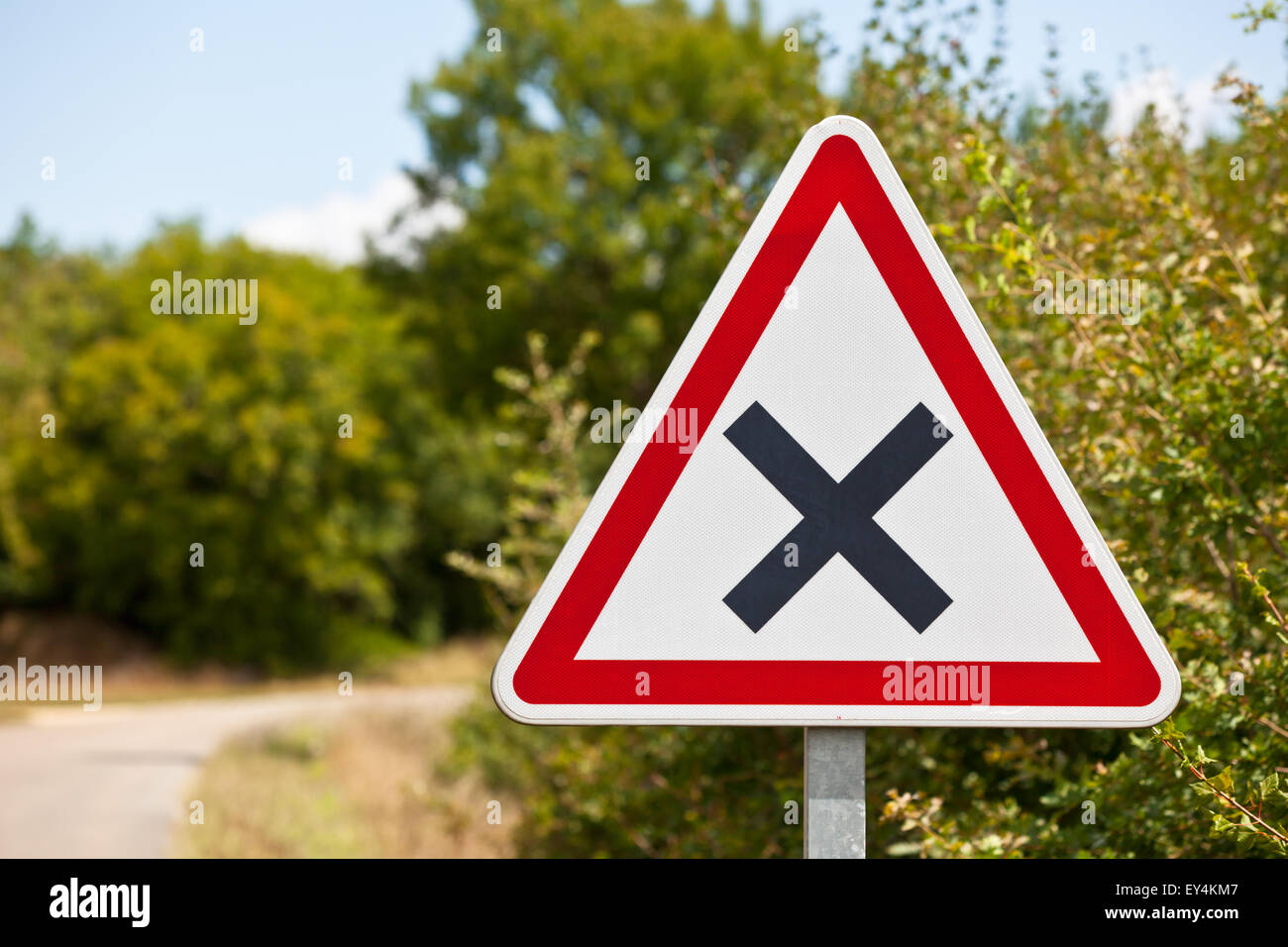 Triangular crossroads road sign on a country road junction - Stock Image