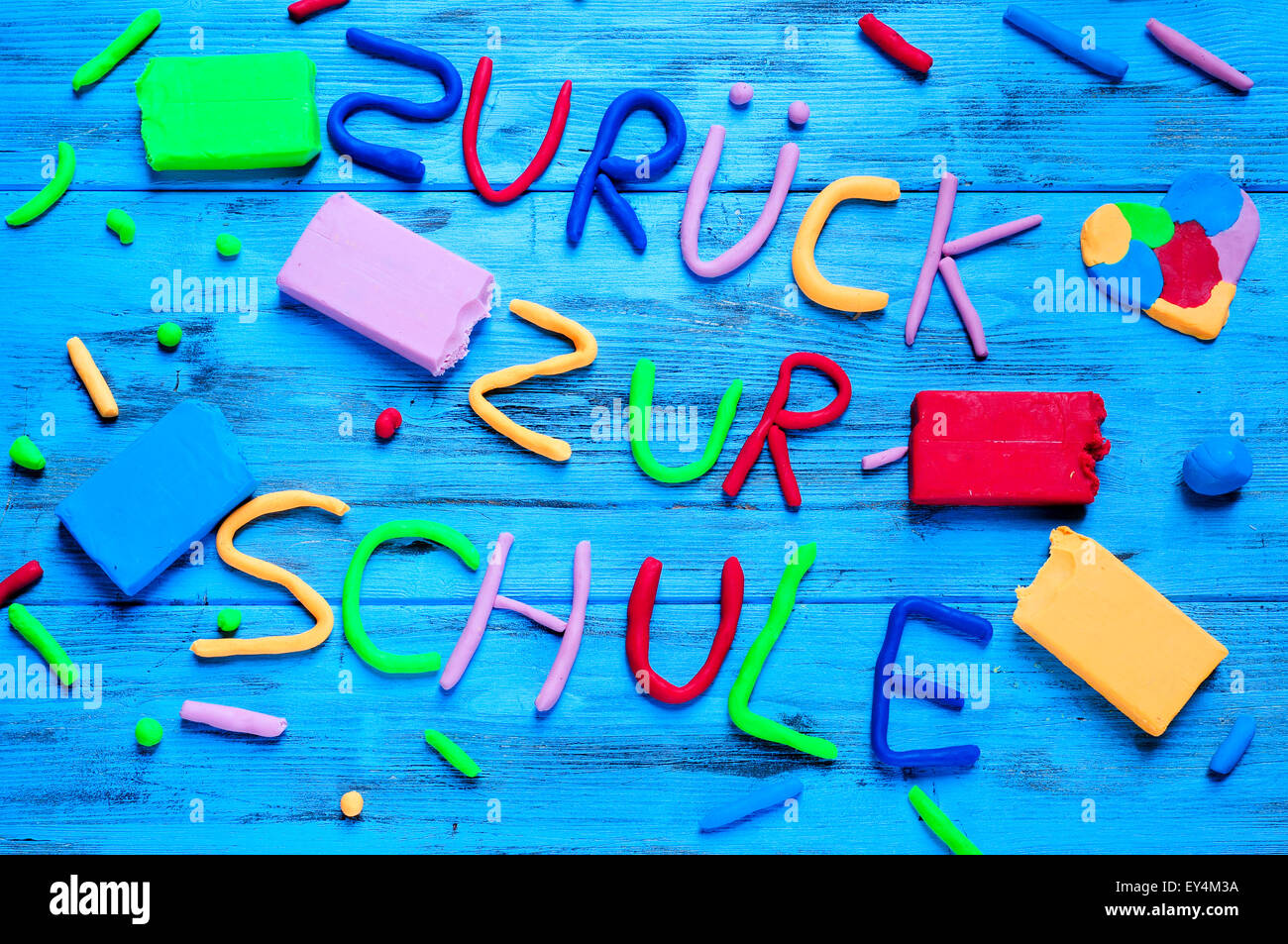 the sentence zuruck zur schule, back to school in german, written with modelling clay of different colors on a blue - Stock Image