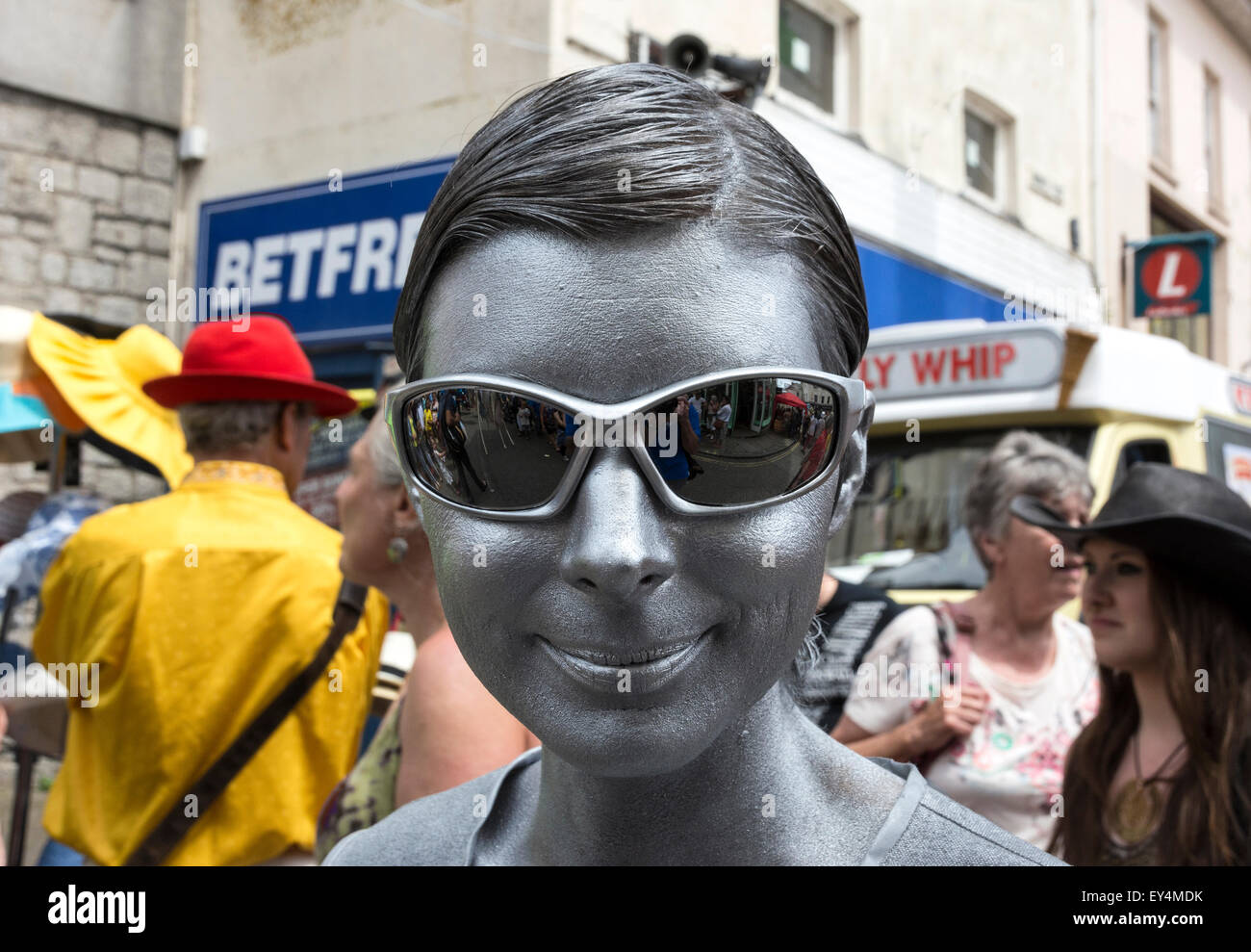 Young female with face painted metallic silver - Stock Image