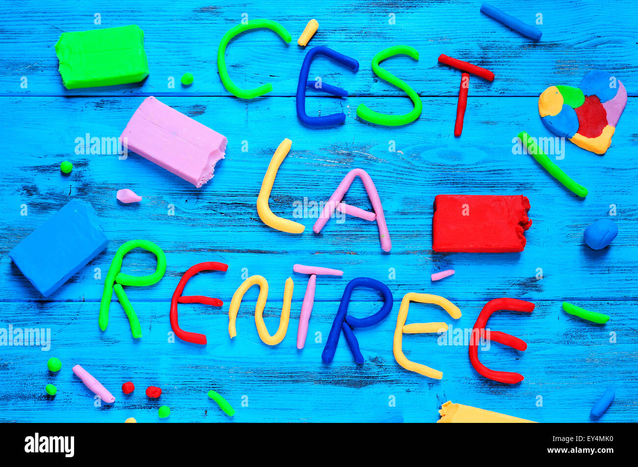 the sentence cest la rentree, back to school in french, written with modelling clay of different colors on a blue - Stock Image
