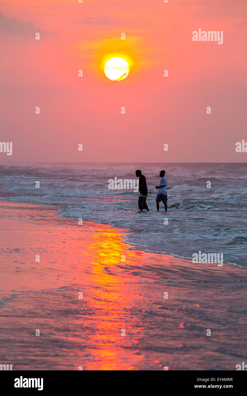 Folly Beach, South Carolina, USA. 21st July, 2015. Two men cool off as the sun rises over the beach on a hot and - Stock Image