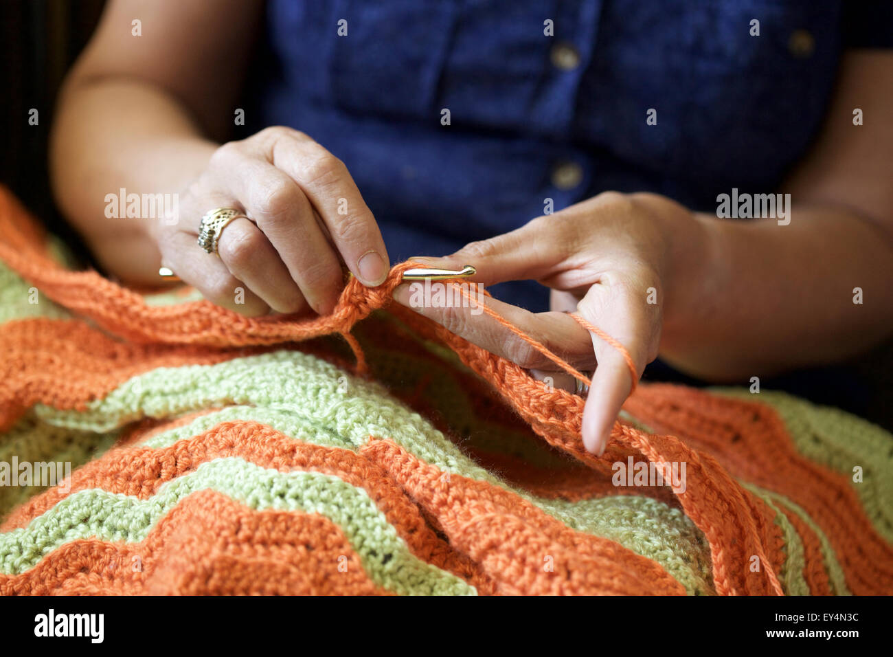 Close up picture of a Caucasian woman crocheting at home - Stock Image