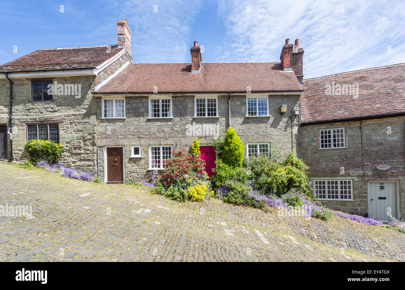 Local style stone cottage with red door in Gold Hill, Shaftesbury, Dorset, UK in summer, location for the Ridley - Stock Image