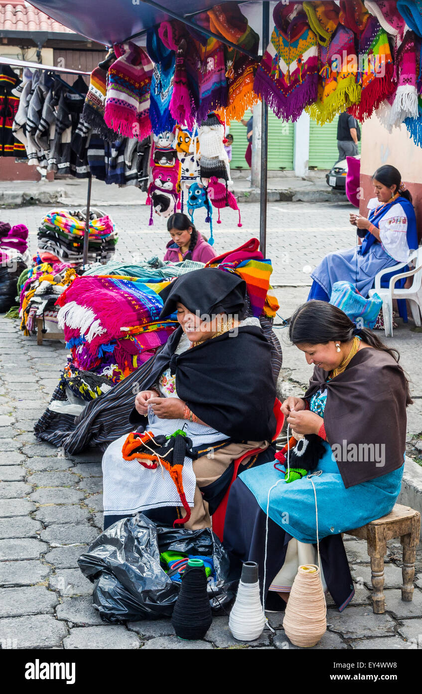 Native women hand knit colorful hats at local market. Otavalo, Ecuador. - Stock Image