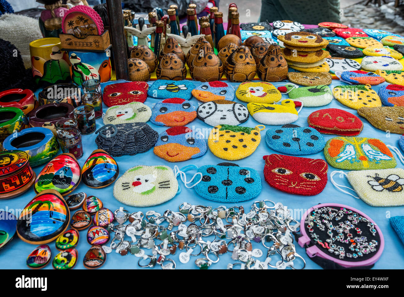 Hand-crafted local souvenirs for sale on a stand at weekend market. Otavalo, Ecuador. - Stock Image