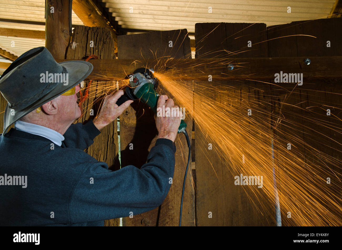 Man using angle grinder producing flying sparks while cutting protruding bolts. - Stock Image