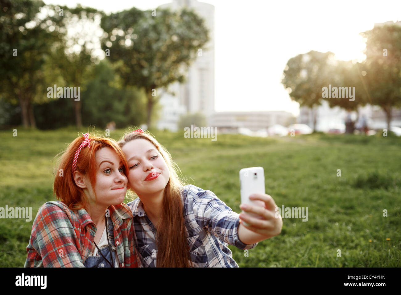 Two Young Hipster Girls Having Fun and Taking Photos (Making Selfie) on Smartphone in a Summer Park at the Sunset. - Stock Image