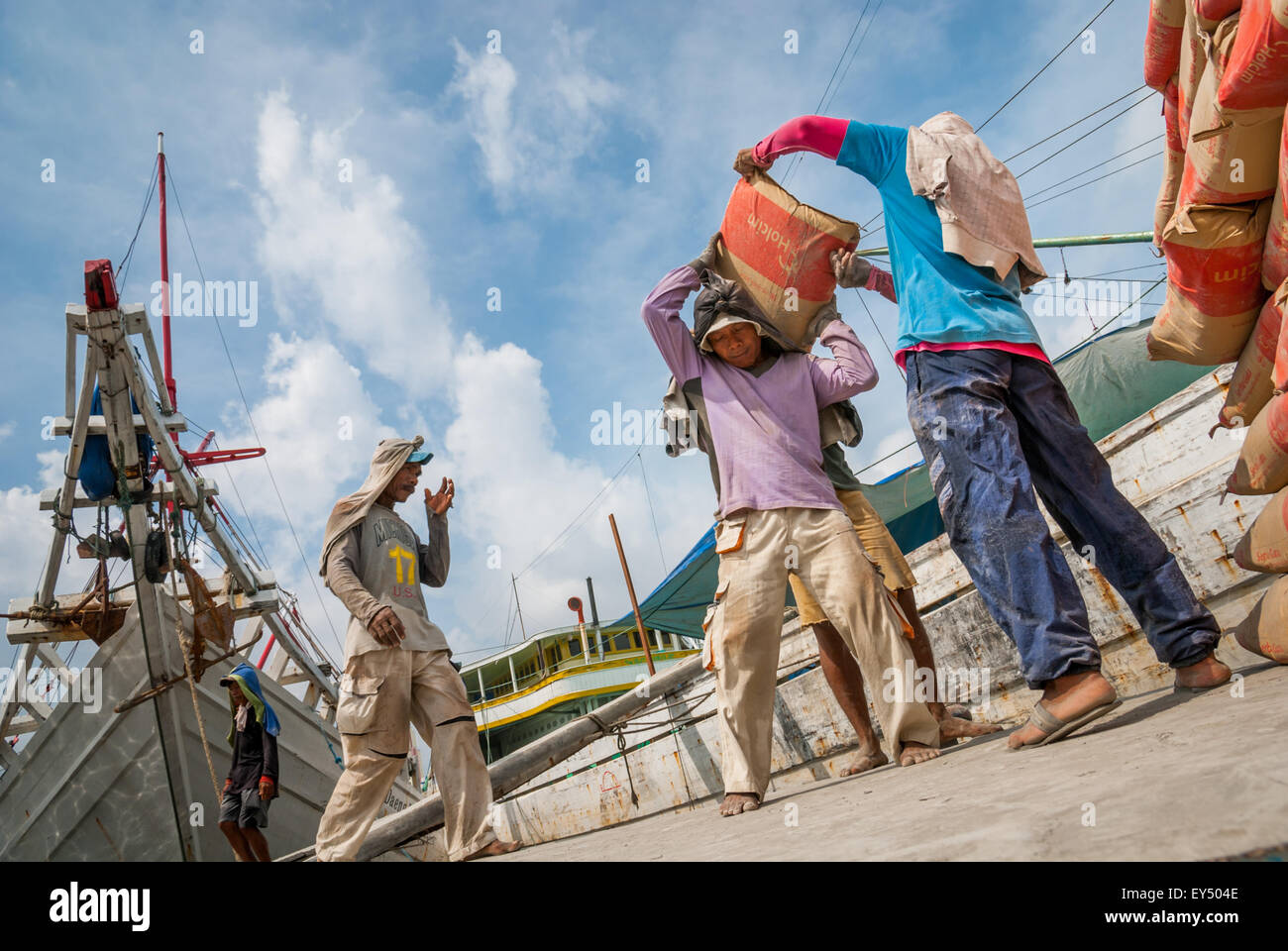 Men transporting cement sacks onto wooden ship on the New Year's Day 2008 at Sunda Kelapa traditional harbour, Indonesia. Stock Photo